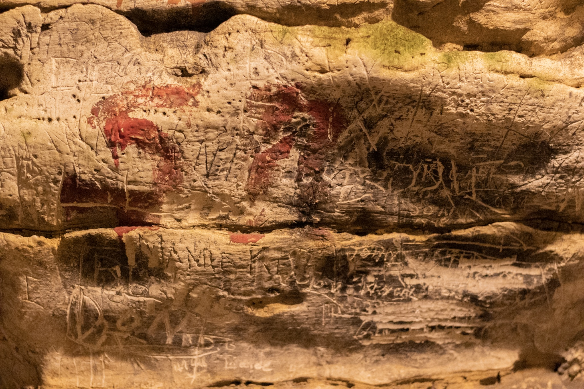 A section of cave wall containing many overlapping and inscrutable inscriptions